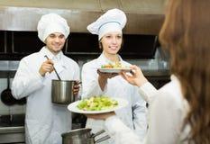 O cozinheiro dá às placas da empregada de mesa Imagens de Stock Royalty Free
