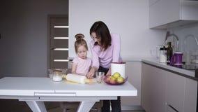 O cozinheiro da filha e da mãe junto na cozinha, filha ajuda a mãe a amassar a massa para panquecas ou cookies Cozinha video estoque