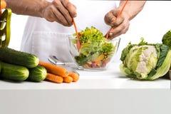 O cozinheiro da mão do homem faz a vegetais da mistura a salada na cozinha Imagens de Stock Royalty Free