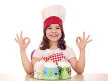 O cozinheiro da menina com bolo doce e a mão aprovada assinam Imagem de Stock