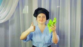 O cozinheiro da mulher em sorrisos do avental, guarda a salada verde ? disposi??o e mostra a classe com m?o vídeos de arquivo
