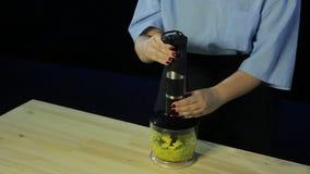 O cozinheiro da mulher em um fundo preto desbasta o quivi e a manga em um misturador video estoque