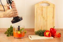 O cozinheiro das mãos está indo aos vegetais do fragmento no misturador Fotos de Stock