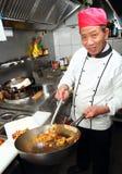 O cozinheiro de Ásia com frigideira chinesa leva embora fotografia de stock