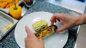 O cozinheiro decora um prato com os peixes no restaurante vídeos de arquivo