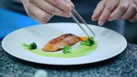 O cozinheiro decora uma faixa dos peixes com vegetais vídeos de arquivo