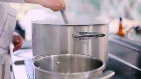O cozinheiro derrama a água com uma concha do potenciômetro no potenciômetro filme