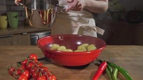 O cozinheiro derrama batatas fervidas quentes para fora da bandeja, cozinhando o alimento, as refeições vegetais, cozinheiro chef filme