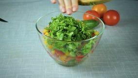 O cozinheiro derrama dentro ingredientes de uma salada da bacia filme