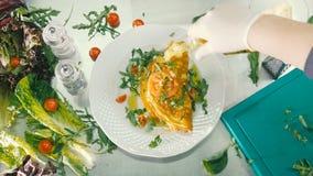 O cozinheiro derrama o óleo na omeleta
