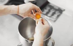 O cozinheiro derrama o ovo na placa de metal fotos de stock