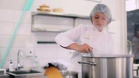 O cozinheiro derrama uma água quente com uma concha no potenciômetro filme