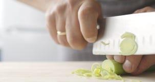 O cozinheiro desbasta finamente alho-porros na placa de madeira filme