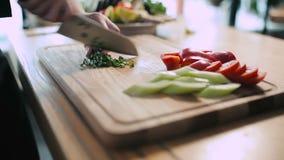 O cozinheiro desbastou cebolas verdes em uma placa de corte filme