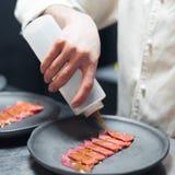 O cozinheiro do cozinheiro chefe do restaurante que prepara o atum listrou a faixa e peixes de derramamento com sause do óleo imagem de stock