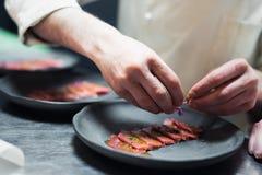 O cozinheiro do cozinheiro chefe do restaurante que prepara o atum listrou a faixa e a salada crambling nos peixes fotos de stock royalty free