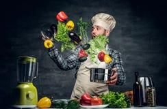 O cozinheiro do homem guarda uma bandeja com os vegetais que voam no ar foto de stock