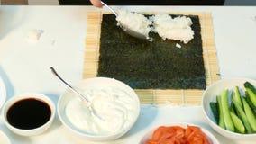 O cozinheiro está colocando o arroz fervido no nori video estoque