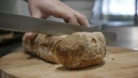 O cozinheiro está cortando o pão video estoque