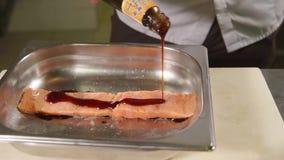 O cozinheiro está derramando o molho chinês da garrafa à faixa salmon em uma placa de metal video estoque