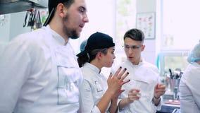 O cozinheiro explica os colegas o processo de cozinhar o prato video estoque