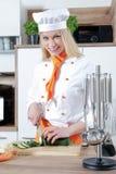 O cozinheiro fêmea bonito novo está cozinhando em uma cozinha algum alimento com carne dos vegetais foto de stock