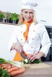O cozinheiro fêmea bonito novo está cozinhando em uma cozinha algum alimento com carne dos vegetais imagem de stock royalty free
