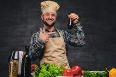 O cozinheiro farpado do cozinheiro chefe come a beringela Foto de Stock Royalty Free