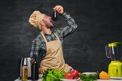 O cozinheiro farpado do cozinheiro chefe come a beringela Imagens de Stock Royalty Free
