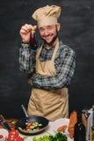 O cozinheiro farpado do cozinheiro chefe guarda a beringela Foto de Stock