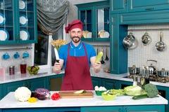 O cozinheiro farpado engraçado no avental e no chapéu guarda a faca e o abobrinha imagens de stock royalty free