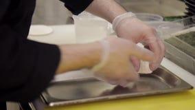 O cozinheiro faz a massa da farinha branca e põe-na sobre a bandeja video estoque