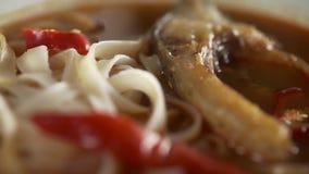 O cozinheiro faz a sopa dos peixes com macarronetes, as ervas frescas e a pimenta, culinária asiática, alimento da dieta, refeiçõ vídeos de arquivo