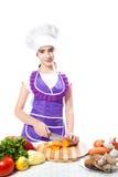 O cozinheiro feliz do cozinheiro chefe da menina corta cenouras Fotos de Stock Royalty Free