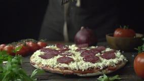 O cozinheiro fricciona o queijo parmesão no movimento lento de pizza de pepperoni filme