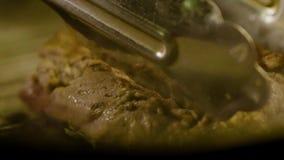 O cozinheiro frita a parte apetitosa de carne grelhada filme