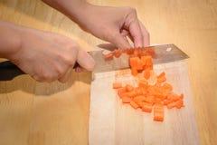 O cozinheiro girava cenouras alaranjadas Imagens de Stock Royalty Free