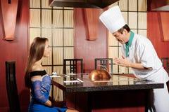 O cozinheiro interage com um convidado fêmea Fotos de Stock Royalty Free