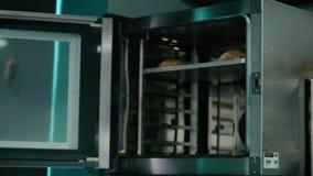 O cozinheiro leva embora o pão do fogão vídeos de arquivo