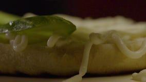 O cozinheiro Makes um Hamburger põe partes de pepino filme
