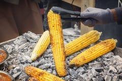 O cozinheiro mantém as cabeças do milho nos carvões ardentes Fast food fotos de stock royalty free