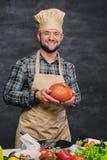 O cozinheiro masculino farpado do cozinheiro chefe guarda a abóbora Imagem de Stock