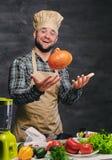 O cozinheiro masculino farpado do cozinheiro chefe guarda a abóbora Fotografia de Stock