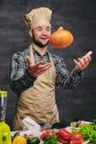 O cozinheiro masculino farpado do cozinheiro chefe guarda a abóbora Imagens de Stock