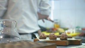 O cozinheiro na cozinha do restaurante prepara petiscos da carne vídeos de arquivo