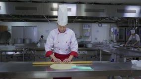 O cozinheiro na tabela do corte desenrola a massa filme