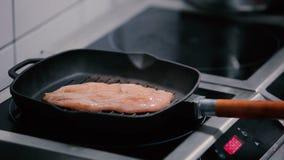 O cozinheiro põe as faixas da galinha sobre a bandeja da grade filme