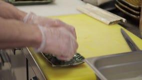 O cozinheiro põe o sushi sobre a placa na cozinha do restaurante filme