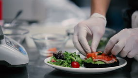 O cozinheiro põe sobre partes de prato de peixes vermelho filme