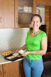 O cozinheiro põr o pão do brinde na bandeja roasting Fotografia de Stock